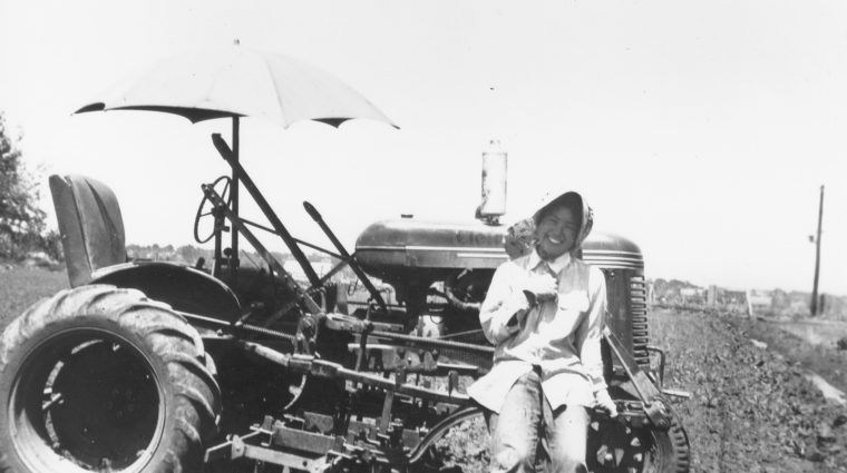 Chiyo Kanemoto sitting on a tractor, wearing a sunbonnet, ca. 1940s.