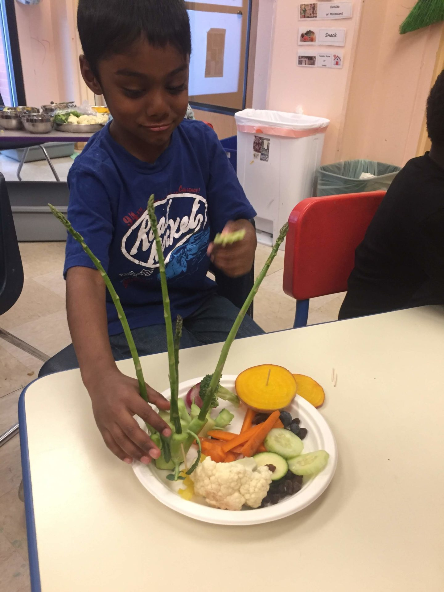 Young boy arranging veggies on a plate.