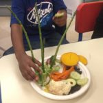 Child building with vegetables