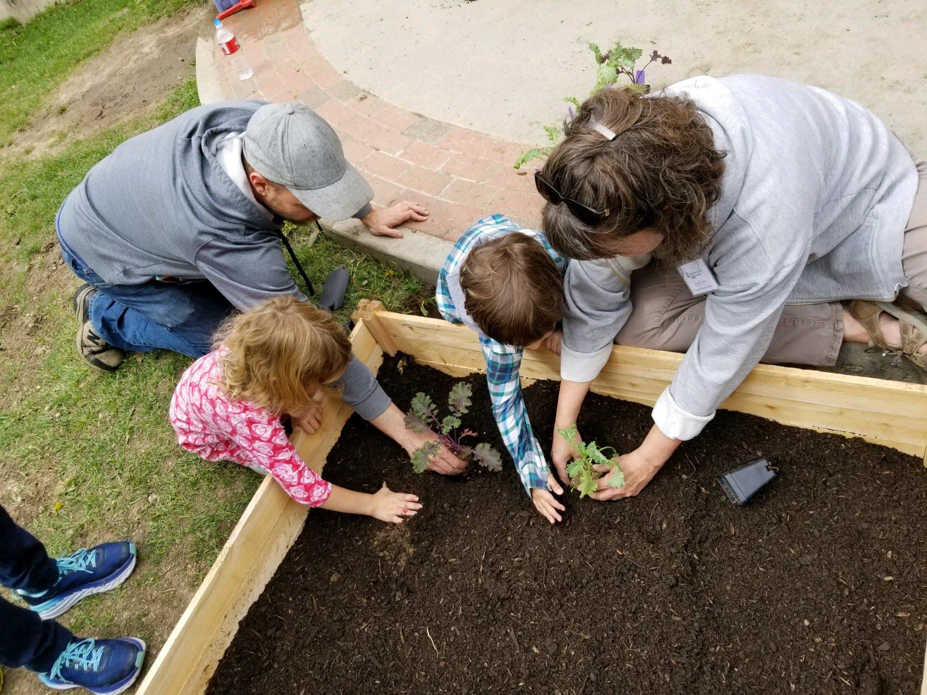Children and Teachers at Children's Alley planting a garden