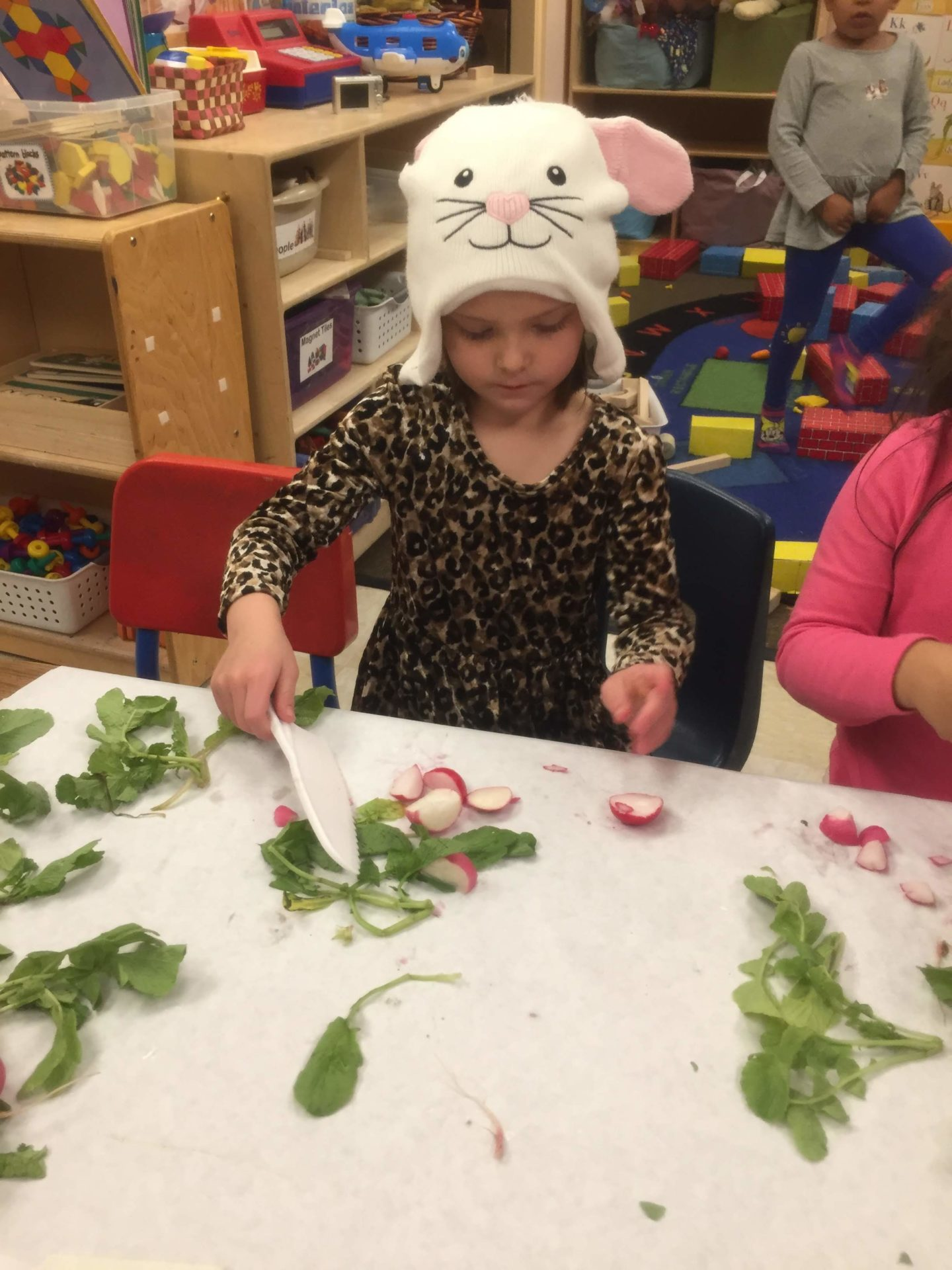 Child helps prepare a healthy meal at Children's Alley
