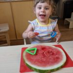 Toddler cutting out shapes from a slice of watermelon